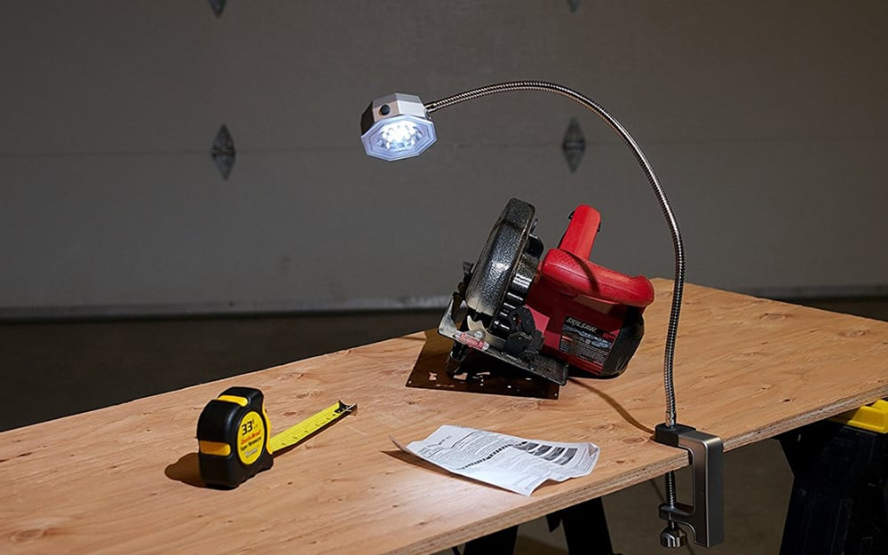A work table in a garage lit by a clamp light.