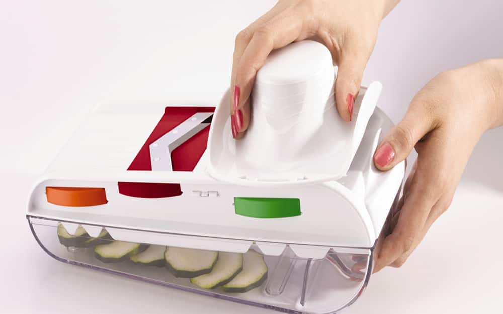 A person slices a vegetable in the food holder of a mandoline slicer.