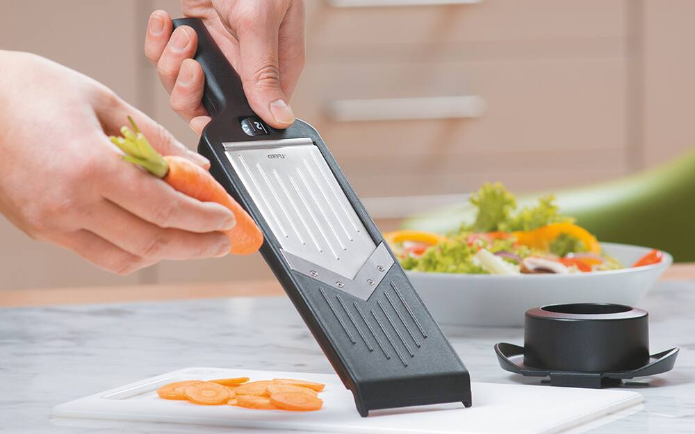 A person uses a handheld mandoline slicer to slice a carrot.