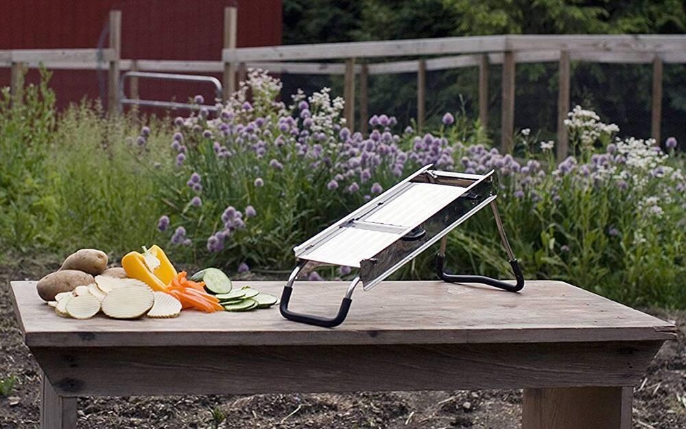 A stand-model mandoline slicer stands on a table next to sliced vegetables.