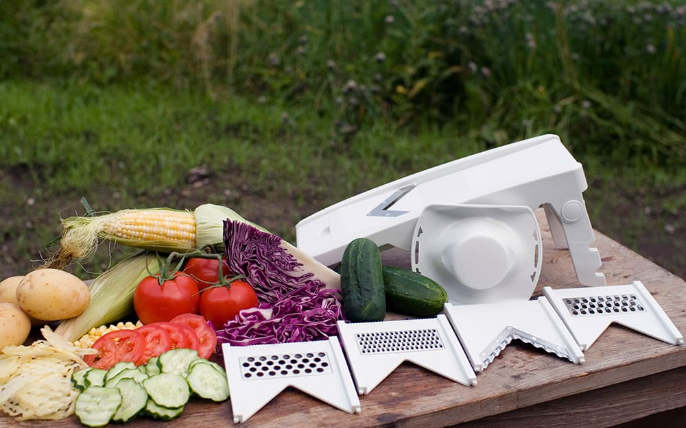 A mandoline slicer stands on a table next to sliced vegetables and detachable blades.
