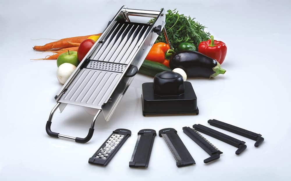 A mandoline slicer stands next to different attachments for slicing and grating.