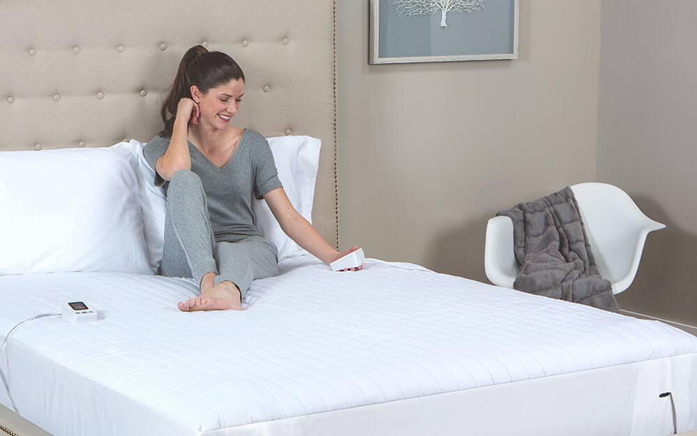 Woman sitting on a mattress pad adjusting the heat.