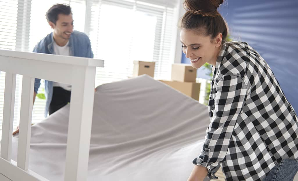 Two people flipping a mattress.
