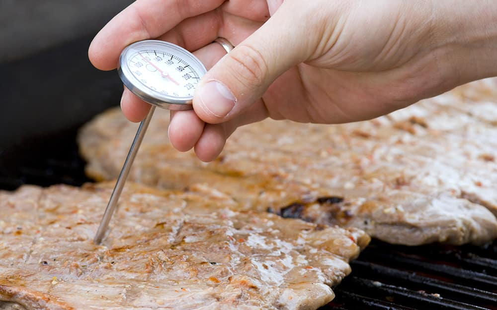 A dial cooking thermometer measures the temperature of meat.