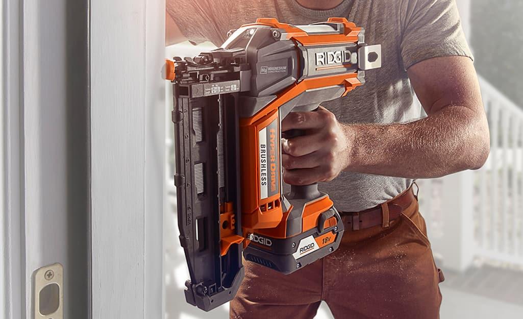 A person using a 15-degree nail gun against a door frame.