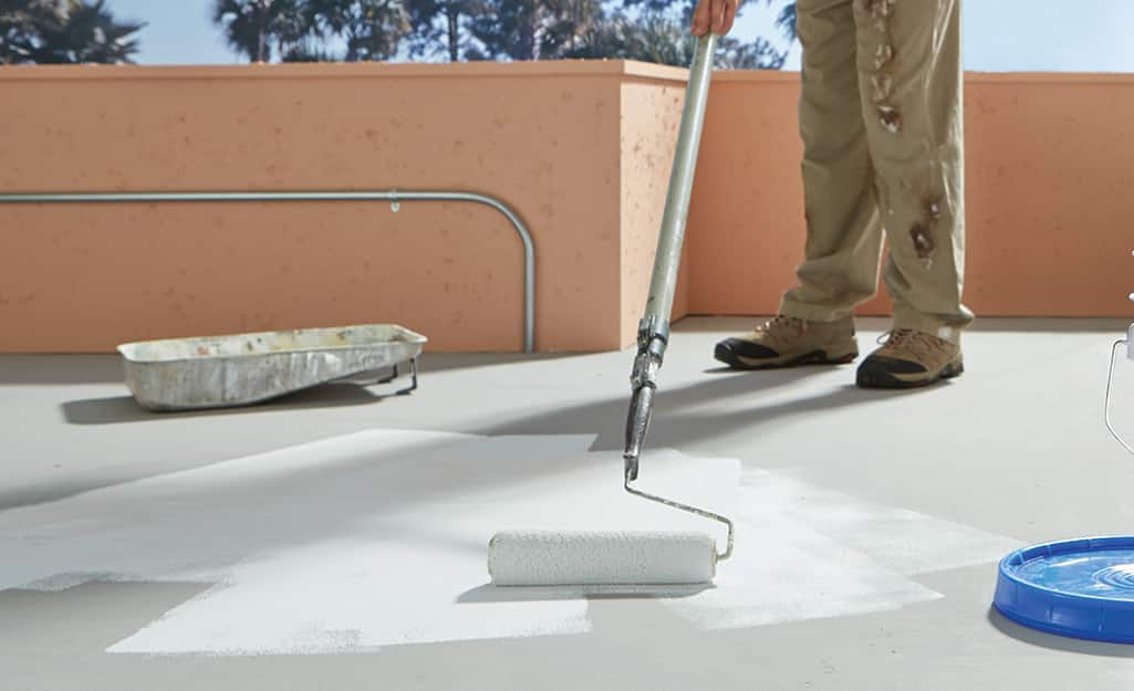 A person applies paint to an outdoor concrete floor.
