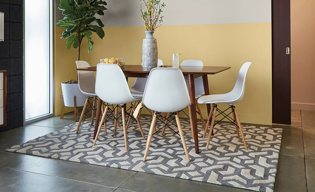 A table and chairs stand on a stained concrete floor.