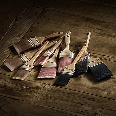 Different types of paint brushes resting on a wooden surface.
