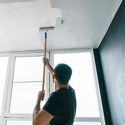 A person paints a ceiling with a paint roller on a frame extension.