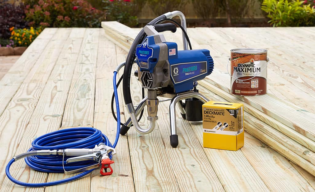 A paint sprayer on a wooden deck.