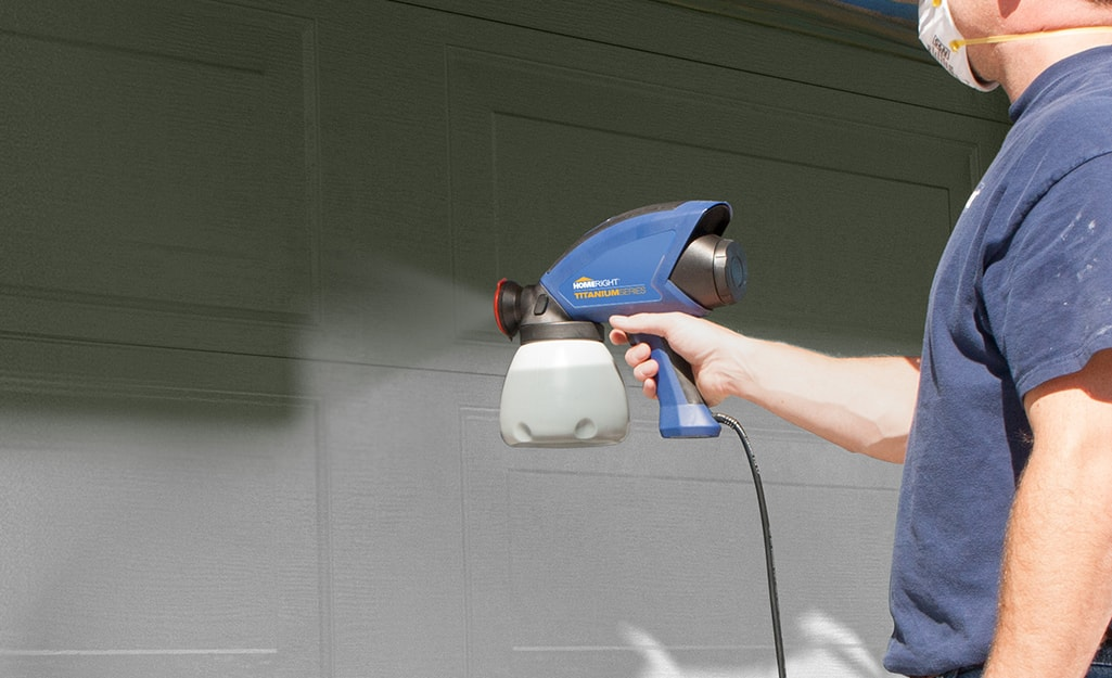 A person using a airless paint sprayer.