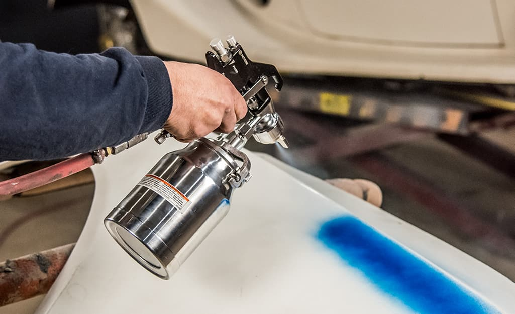 A person using a compressed air paint sprayer.