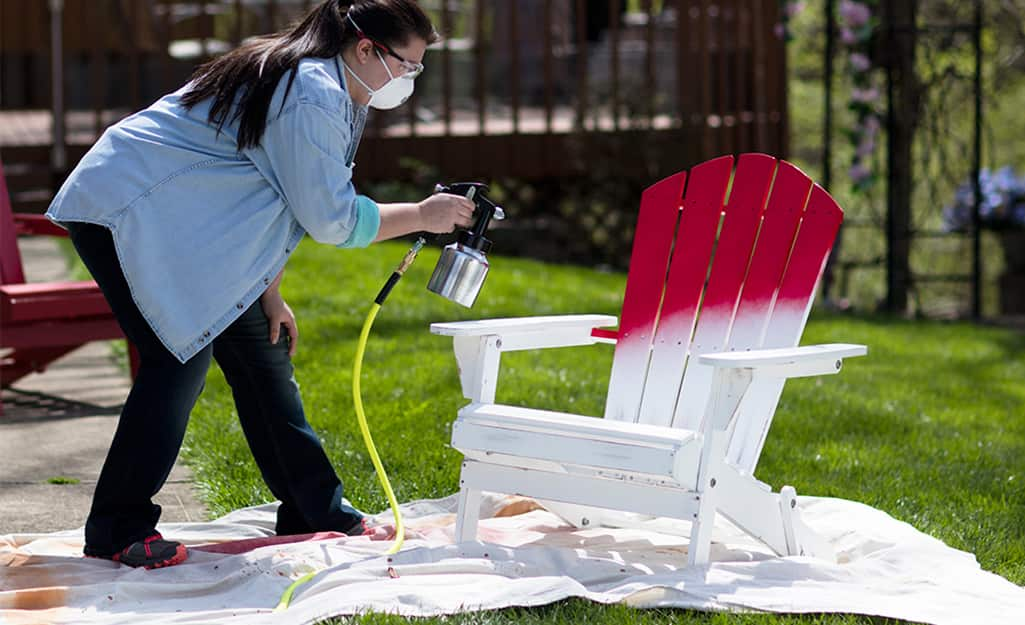 A woman using a paint sprayer to paint an an Adirondack chair.