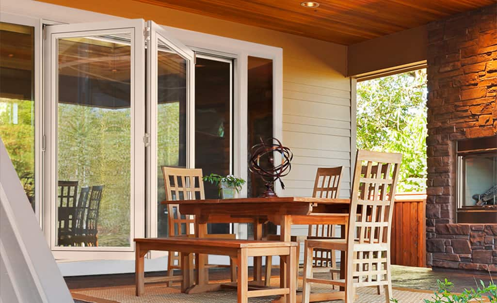 A folding patio door on a patio with wood and brick trim.