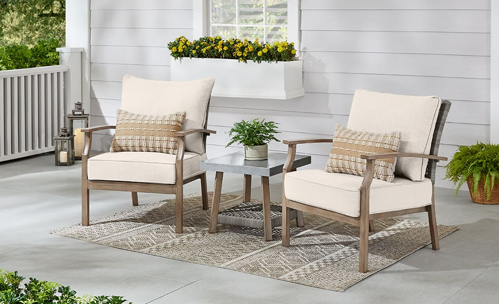 Two chairs and a side table with a beige rug on a patio.