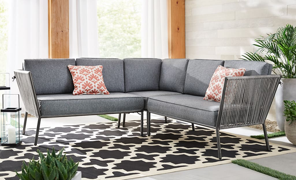 Gray sectional sofa with red patterned pillows on a patio.