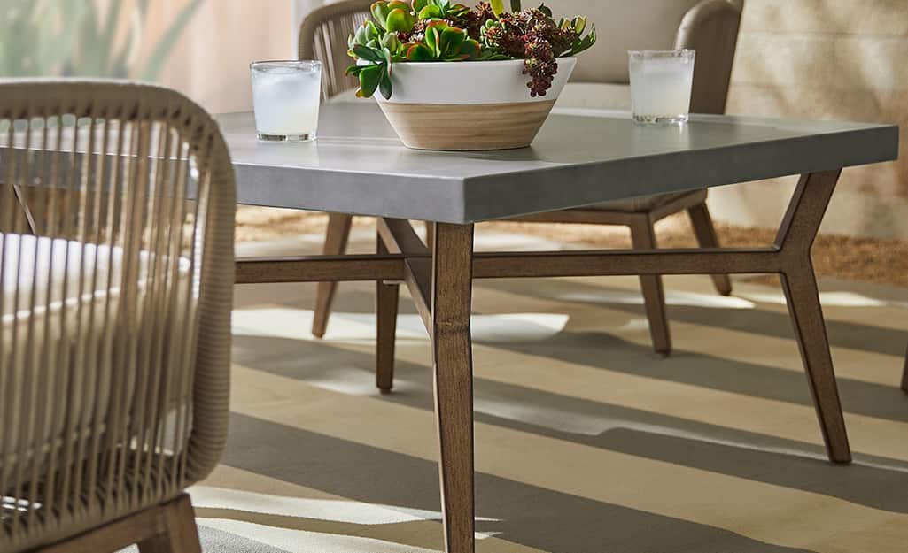 A coffee table with a gray top and wooden legs on a patio.