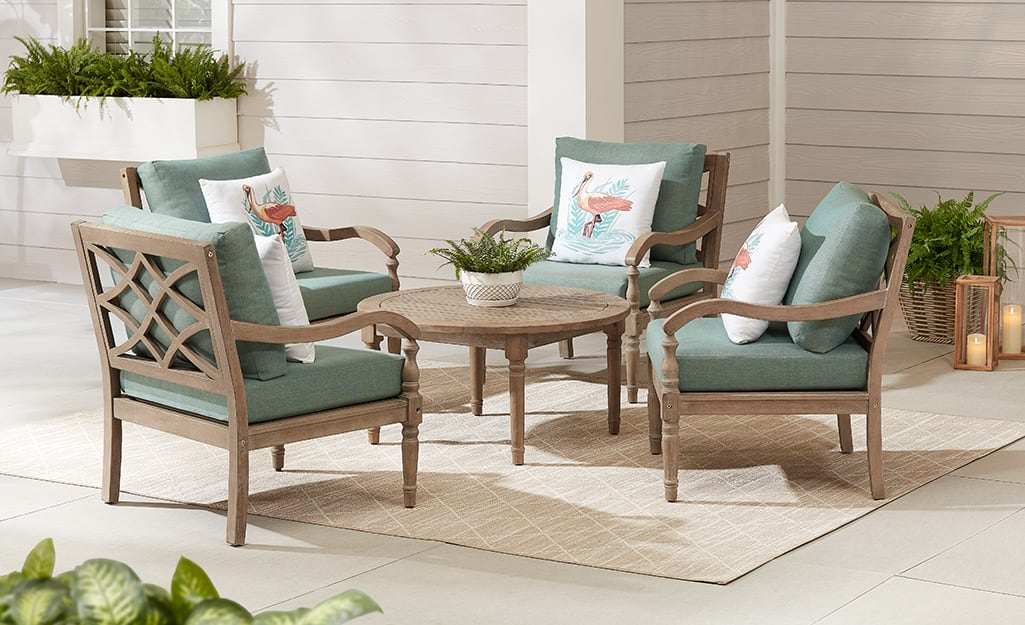 A bronze patio set with cushion chairs and a round table on a patio.