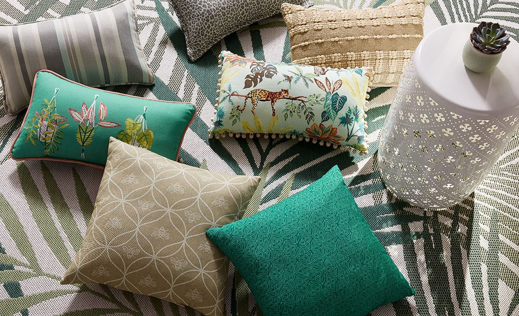 Pillows and other patio accessories on a green and white rug.