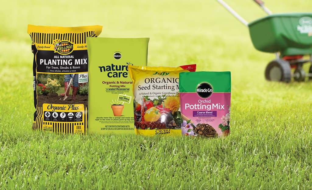 Four bags of different types of potting soil sitting on a green lawn with a fertilizer spreader behind them.