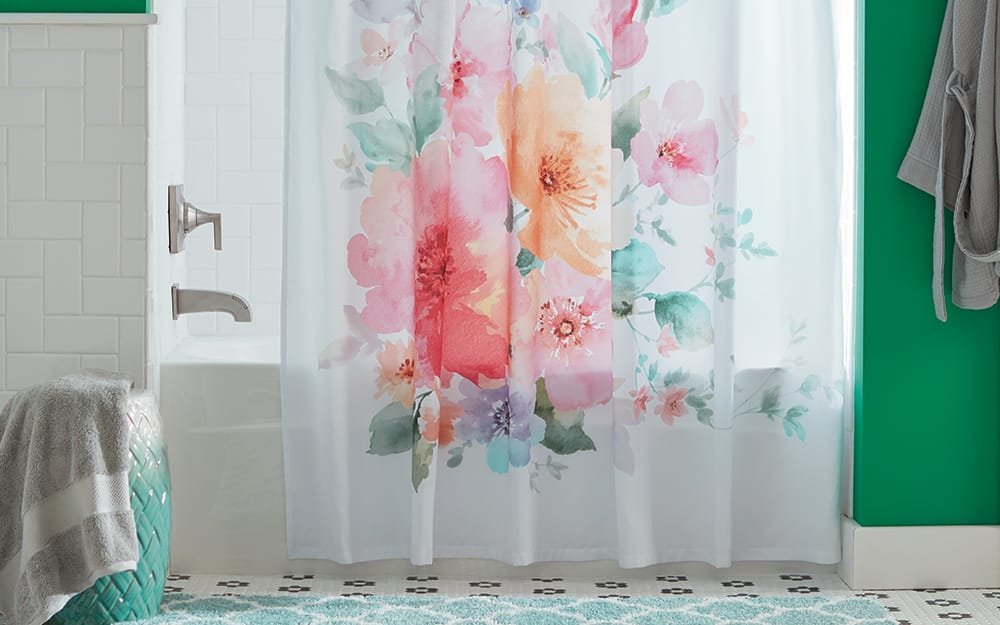 A floral shower curtain hanging over a bathtub