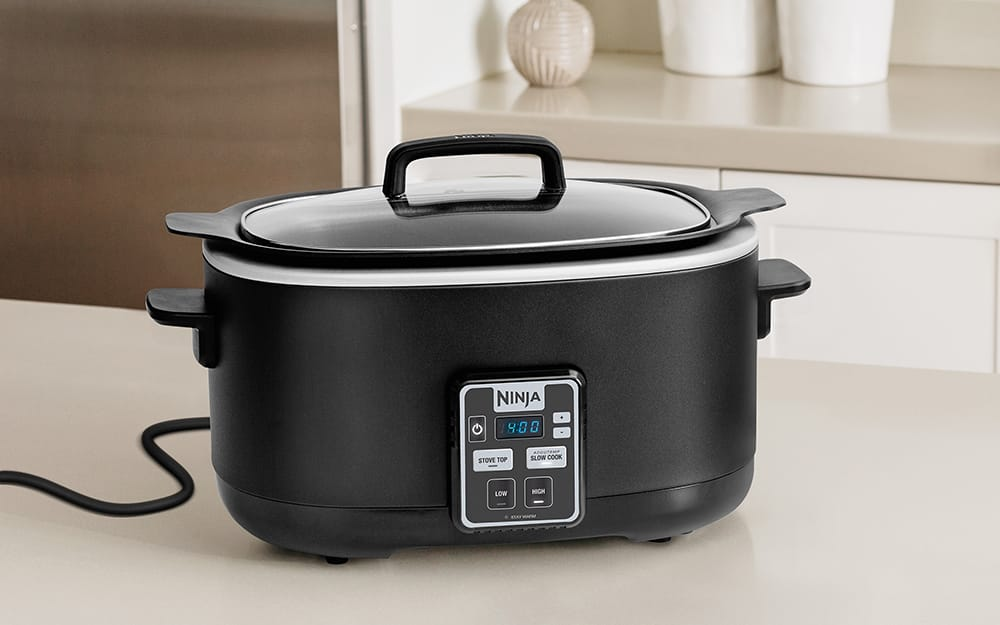 A black slow cooker on a counter.