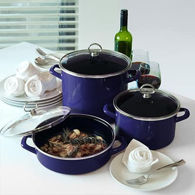 Two stock pots, a bottle of wine and two glasses and a skillet of food on a tabletop.