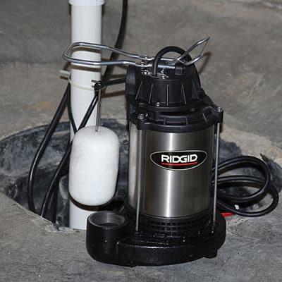 A submersible sump pump on a basement floor.