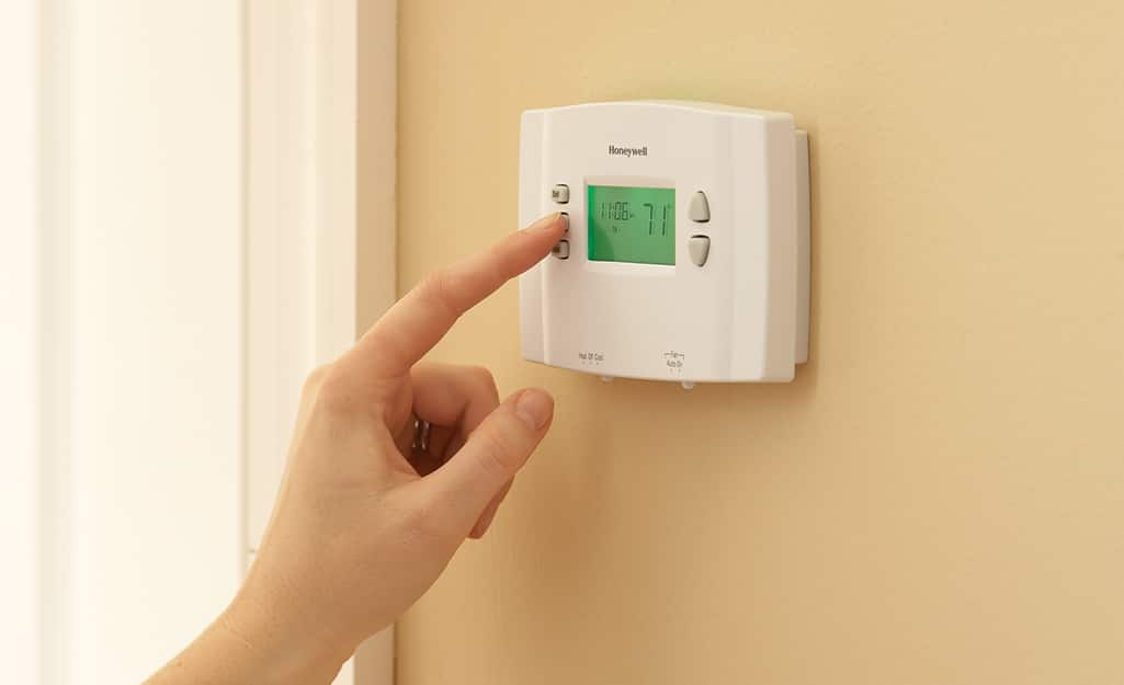 A person pressing a button on a manual thermostat.
