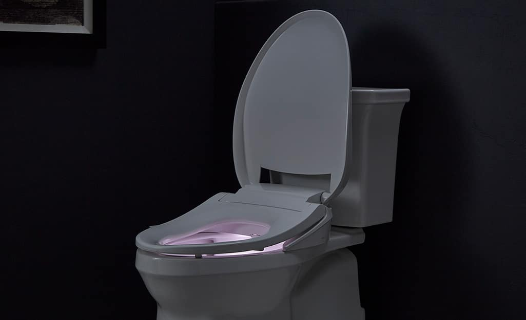 A toilet with a lighted seat in a dark room.
