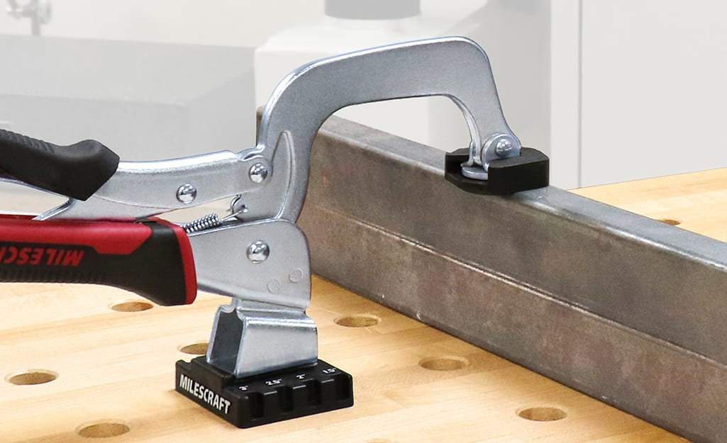A clamp is used on a piece of metal.