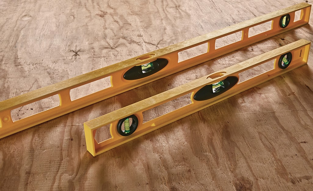 Two levels displayed side by side on a piece of wood.