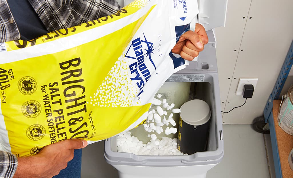 A person adds salt pellets to a water softener.