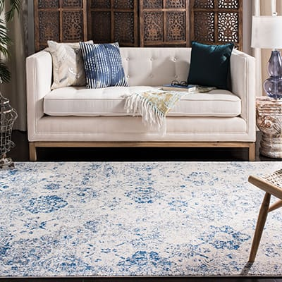A living room with blue decor including pillows and a rug.
