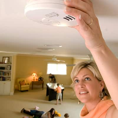 A person adjusts a carbon monoxide detector mounted on a ceiling.