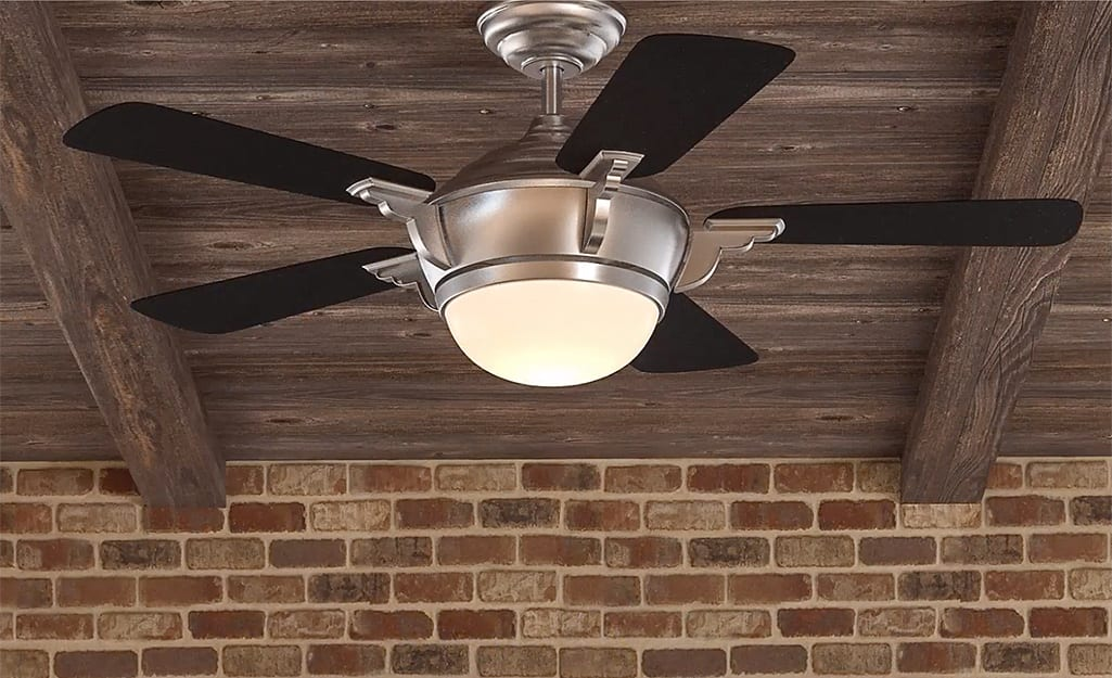 A large ceiling fan with a light hangs from a ceiling.