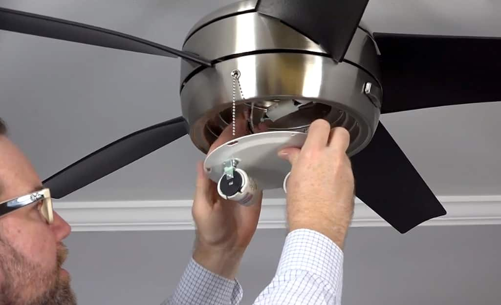A person removing the light assembly from a ceiling fan.