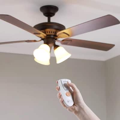 A person uses a remote control on a ceiling fan.