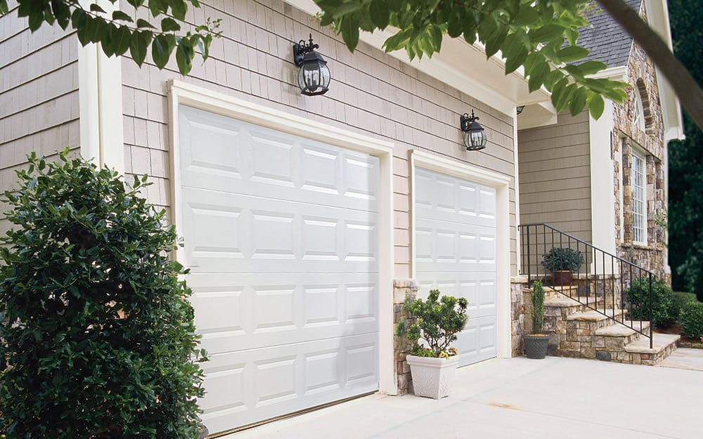 A garage exterior featuring outdoor wall lights