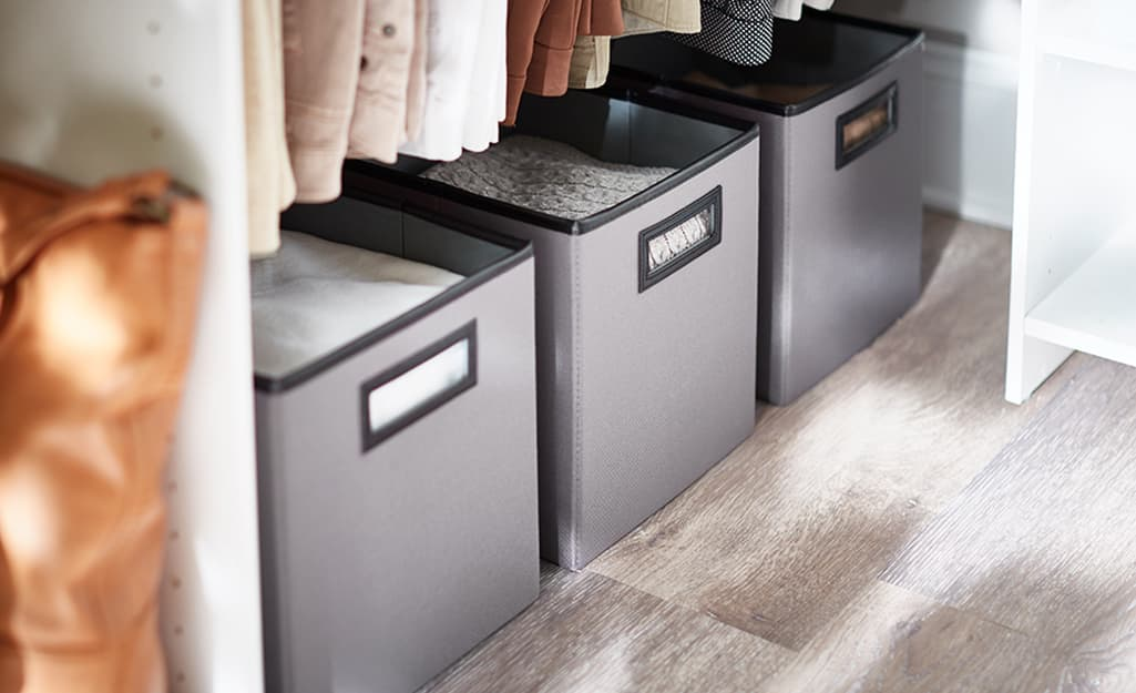 A row of fabric cube storage along the floor of a closet.