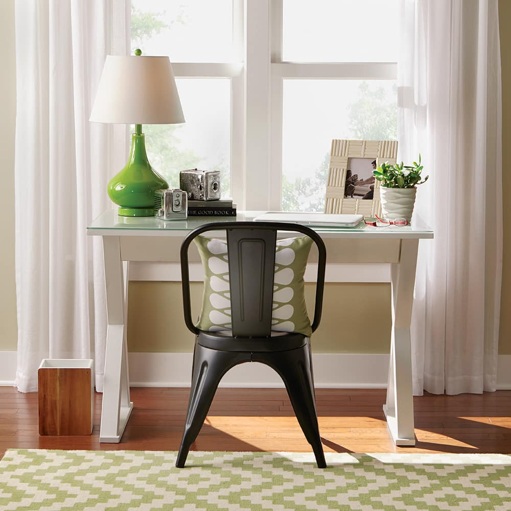 Black chair and white desk sitting in front of a window.