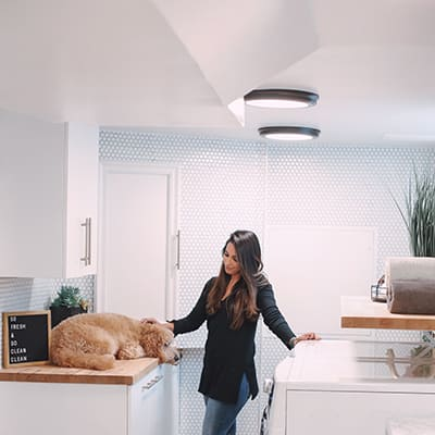 A woman petting a dog in a bright laundry room.