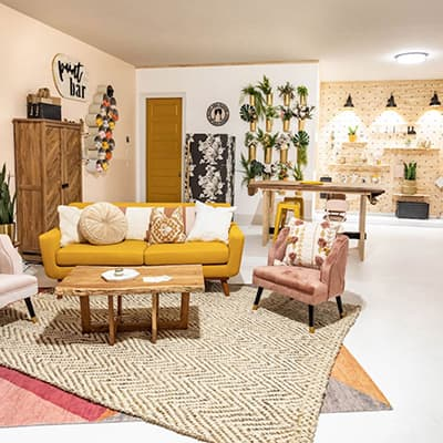 A garage decorated with a seating area, workbench, and wooden pegboard accent wall.