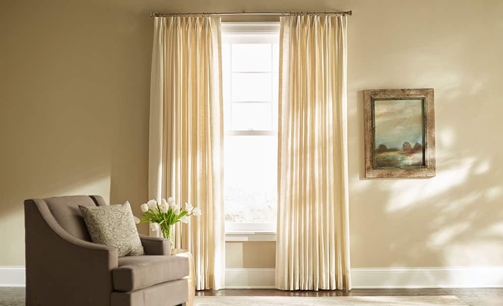 Cream-colored pleated curtains over a living room window.