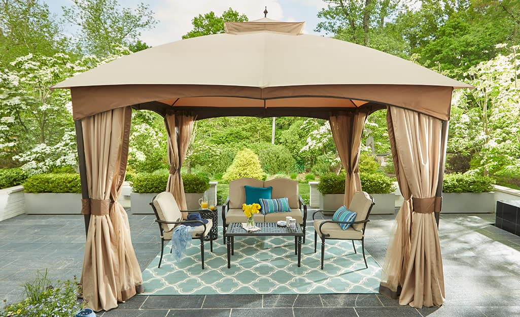 Outdoor curtains around an outdoor dining table and chairs.