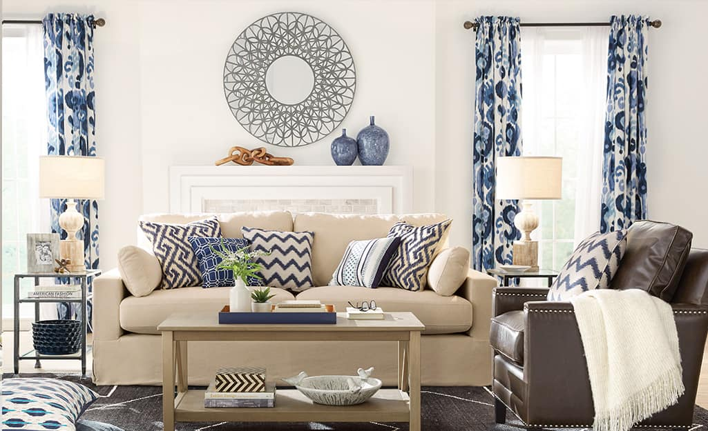 Blue and white patterned curtains over the windows in a living room.