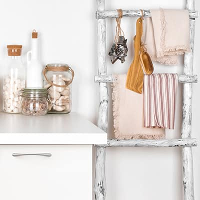 Old ladder painted distressed white holding kitchen towels.