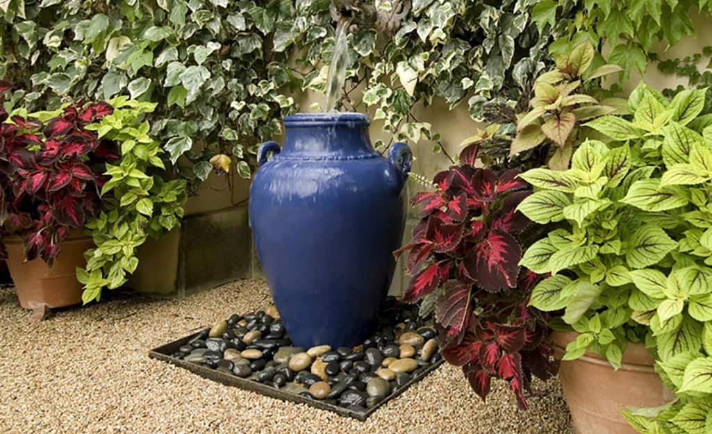 Decorative river rocks surrounding a blue garden urn on a bed of small stone gravel.