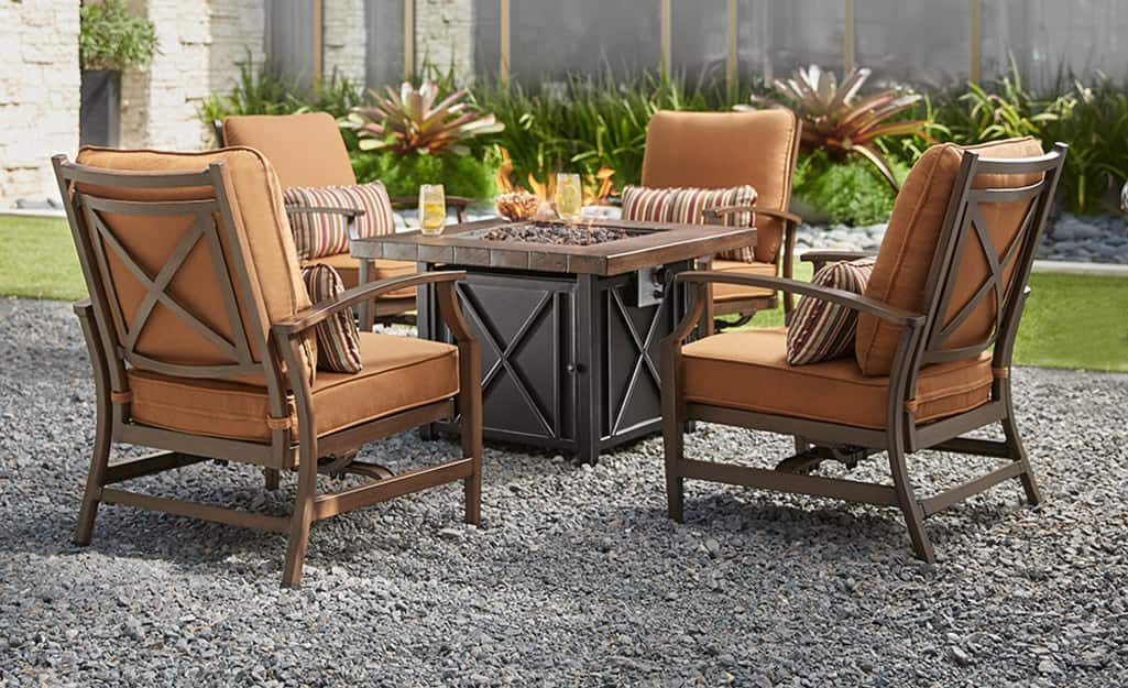 A set of garden furniture on an outdoor gravel surface.